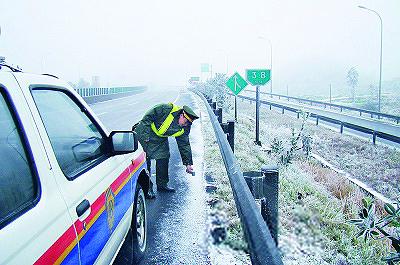 路政队员在京珠北高速公路梅花至大桥路段测量路面