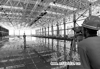珠海制造基地已安装完毕的车间吊顶下,施工人员在检测地面基础平整度.